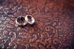 在棕色背景的婚戒特写镜头 免版税库存照片