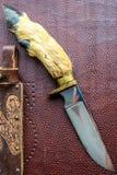 在棕色背景的手工制造猎刀 免版税库存图片