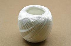 在棕色背景的白色塑料绳索 库存照片
