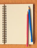 在棕色背景的笔记本和颜色铅笔 免版税库存照片
