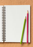 在棕色背景的笔记本和颜色铅笔 库存图片