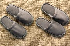 在棕色背景隔绝的两个对灰色自创拖鞋 免版税库存照片