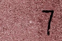 在棕色脏的水泥墙壁上的第七 免版税库存图片