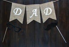 在棕色葡萄酒木背景的愉快的父亲节横幅 词爸爸在旗子wriiten 免版税库存照片