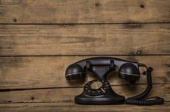 在棕色葡萄酒背景的老黑怀乡电话concep的 免版税库存照片