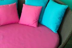 在棕色藤条沙发的桃红色和蓝色枕头 库存照片