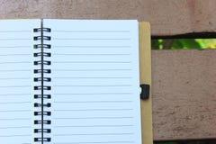 在棕色长凳的笔记本 库存照片