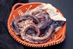 在棕色陶器的未加工的章鱼在黑背景 库存图片