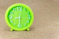 在棕色麻袋布背景的绿色闹钟 免版税库存图片