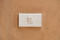 在棕色水泥墙壁背景的白色开关 库存图片