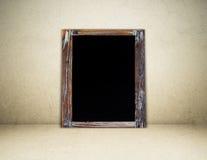 在棕色水泥墙壁背景的空白的葡萄酒粉笔板 免版税库存图片