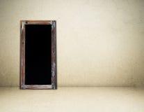 在棕色水泥墙壁背景的空白的葡萄酒粉笔板 免版税库存照片