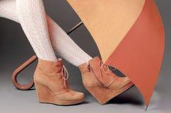 在棕色绒面革起动的女性腿在灰色bac的一把伞下 图库摄影