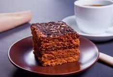 在棕色platewith咖啡的可口巧克力蛋糕在黑桌上的 库存照片