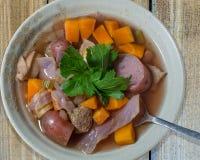 在棕褐色的碗的Crockpot炖煮的食物在木台式视图 图库摄影