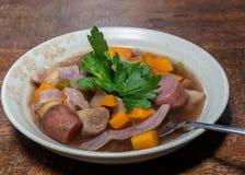 在棕褐色的碗的Crockpot炖煮的食物在木桌上 库存照片