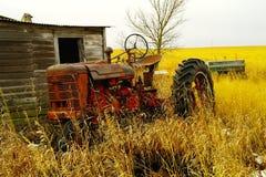 在棚子旁边的一台老拖拉机 库存图片