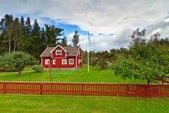 在森林一边的瑞典村庄房子 库存图片