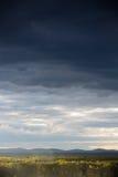 在森林下的风雨如磐的天空 免版税库存照片