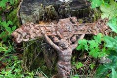 在森林丢失的老生锈的十字架 免版税库存照片