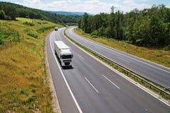 在森林之间的高速公路有三辆近来白色卡车的 库存图片
