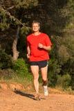 在森林公路的年轻人赛跑春天 图库摄影