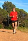 在森林公路的年轻人赛跑春天 免版税库存图片