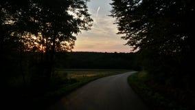 在森林公路的日落 免版税库存照片