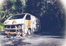 在森林公路的被击毁的老车 库存照片