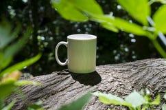 在森林地树的一个独奏空白的加奶咖啡杯子 库存图片