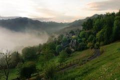 在森林小山村庄的有薄雾的日出 免版税库存照片