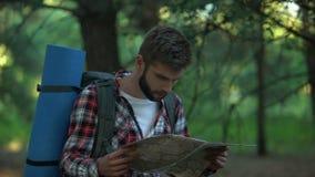在森林尝试失去的被迷惑的徒步旅行者读方向的地图,情志过极 股票视频