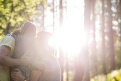 在森林拥抱与阳光的家庭 免版税库存图片