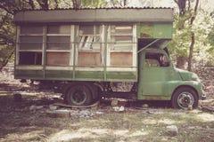 在森林放弃的老露营车 葡萄酒 免版税库存照片
