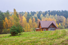 在森林旁边的议院在秋天 免版税库存图片