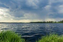 在森林湖的天空在风暴雨前 免版税库存照片