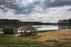 在森林湖的岸有公共浴室和gazeb 库存图片