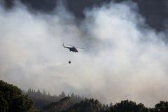 在森林火灾的直升机繁忙的滴下的水 免版税库存照片