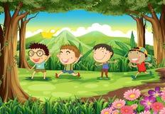 在森林的四个嬉戏的孩子 免版税库存照片