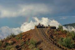 在森林的彩虹,自然现象,岩石和树、明亮的颜色在彩虹,雨和多云天空 免版税库存照片