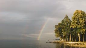 在森林的美丽的彩虹由湖 免版税库存图片