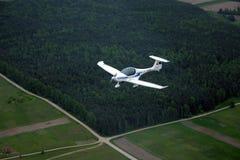 在森林背景的飞行的小飞机 免版税图库摄影