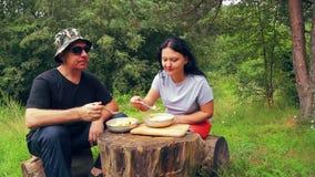 在森林边缘的男人和妇女游人坐下落的树并且吃水果沙拉并且敬佩自然 股票视频