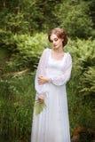 在森林边缘的美丽的女孩一件长的白色礼服的 免版税库存照片