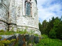 在森林边缘的老被破坏的石教会 库存图片