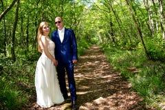 在森林道路的婚礼夫妇 免版税库存照片