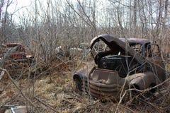 在森林里和其他车放弃的一辆老卡车在冬季期间 库存图片