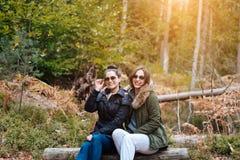 在森林里坐的下来两个美丽的女孩 免版税图库摄影