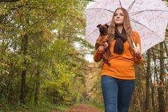 在森林里塑造有一条狗的女孩 免版税库存图片