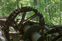 在森林里放弃的古色古香的抽油装置 图库摄影
